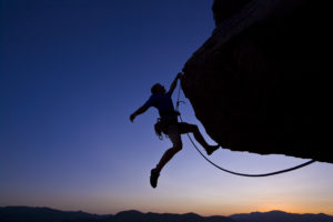 Climber dangling against sunset horizon.